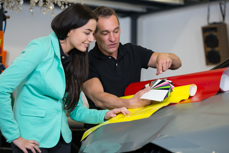 Car wrapping professional consulting a client about vinyl films or foils photo