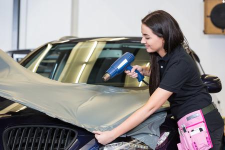 flatten: Car wrappers using heat gun to flatten vinyl film or foil