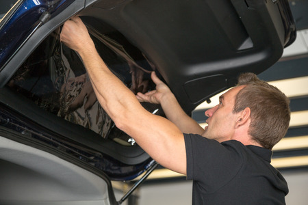 tinting: Car wrapping specialist attaching tinting foil to car window