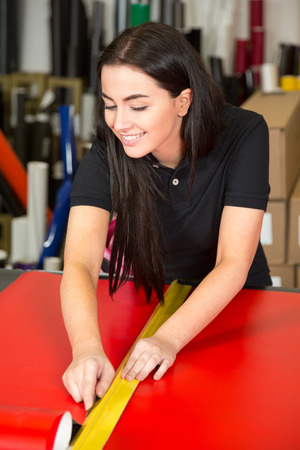 box cutter: Car wrapping specialist cutting vinyl foils with box cutter Stock Photo