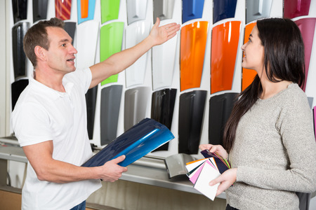 car retailer: Salesman consulting a customer about car wrapping foils in different colors Stock Photo