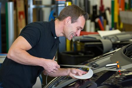 車ラッピングのワーク ショップの労働者が車のボンネットに箔を接着剤します。