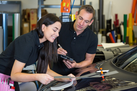 instructing: Worker instructing female apprentice in car wrapping workshop
