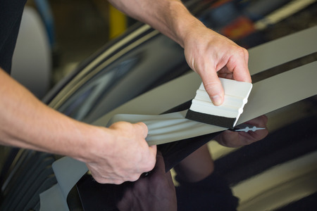 squeegee: Car wrapper straightening wrapping foil with a squeegee to remove air bubbles