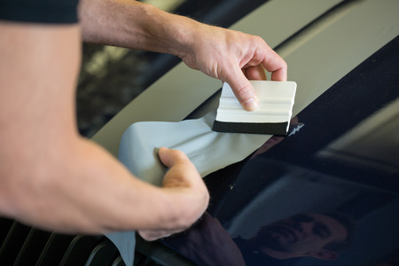 vinyl: Car wrapper straightening wrapping foil with a squeegee to remove air bubbles