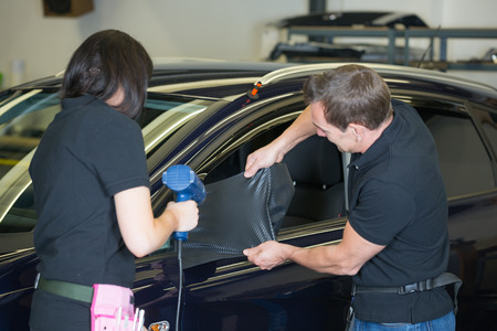 Team of car wrapping specialists wrapping side mirror with carbon foil photo