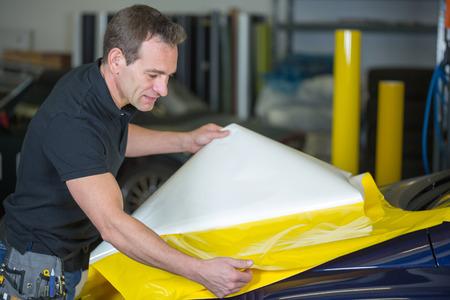 Auto wrapper voorbereiding gele folie om een voertuig wrap