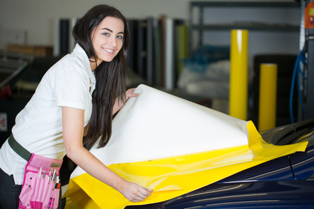 Car wrapper preparing yellow foil to wrap a vehicle