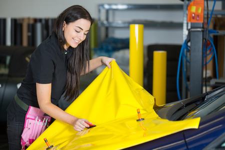 wrapping: Car wrapping specialists straightening vinyl foil or film to remove ari bubbles
