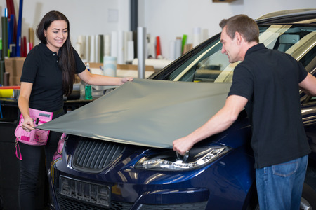 Car wrapping specialists wrapping a vehicle with grey vinyl film or foil Stock Photo
