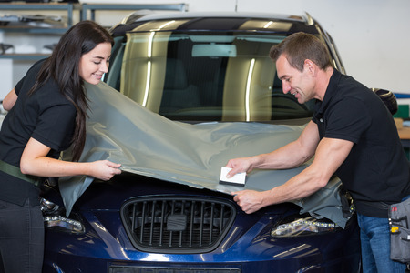 wrappings: Car wrappers using squeegee to straighten vinyl foil  Stock Photo