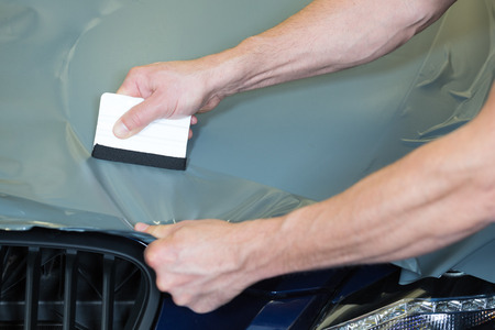 Car wrappers using squeegee to straighten vinyl foil  Stock Photo