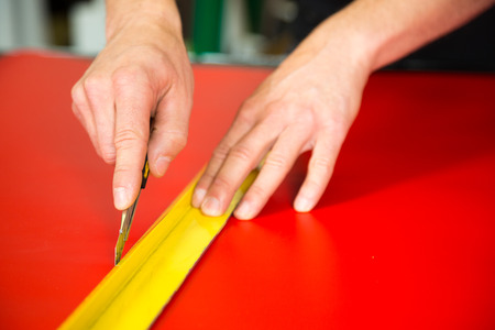 Car wrapping specialist cutting vinyl foils with box cutter Stock Photo