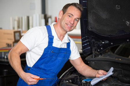 auto repair: Mechanic checking oil level at a car in garage Stock Photo
