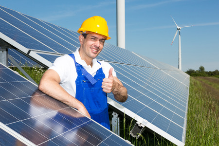 Photovoltaic engineer showing thumbs up at solar energy array photo