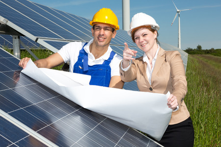 Photovoltaic engineer and contractor with construction plan at solar panels