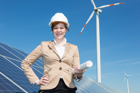 photovoltaic power station: architect or engineer posing at solar panels in wind farm