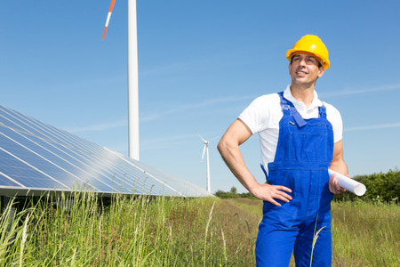 installer: engineer or installer posing with wind turbine and solar panels Stock Photo