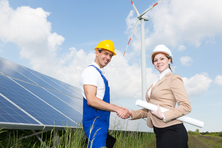 Two engineers shake hands in front of solar panels and a wind turbine photo