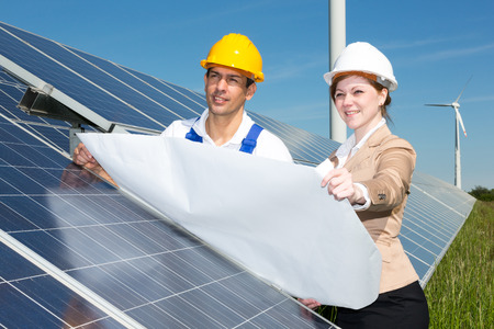 female architect: Photovoltaic engineer and contractor with construction plan at solar panels