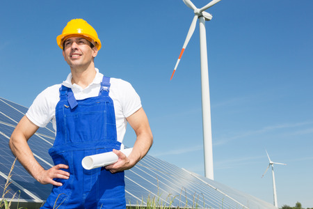 engineer or installer posing with wind turbine and solar panels photo