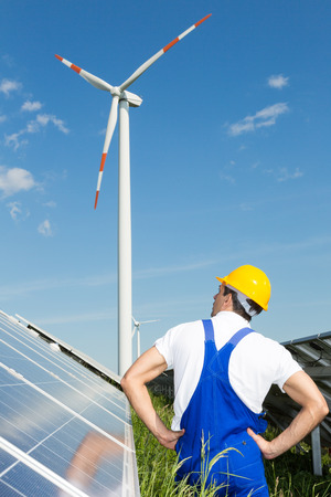 Engineer in front of solar panels looking at wind turbine photo