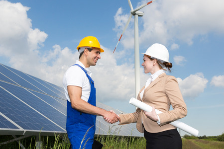 photovoltaic power station: Two engineers shake hands in front of solar panels and a wind turbine