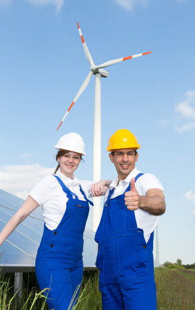 Two engineers posing with wind turbine and solar energy panels giving thumbs up photo