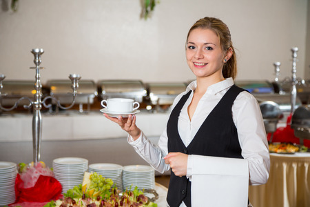 waitress from catering service  in restaurant posing with soup dish photo