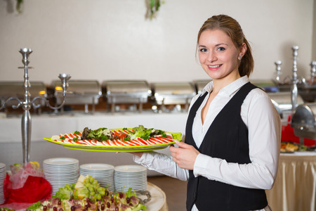 Catering service employee or waitress posing with tray for buffett