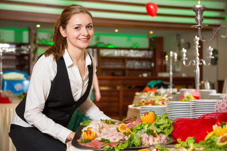 Catering service employee or waitress preparing a buffet Stock Photo