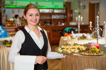 Catering servis zaměstnanec nebo servírka pózují s tácem předkrmů
