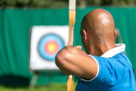 Bowman or archer aiming at target with bow and arrow
