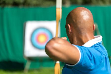 hombre disparando: Bowman o arquero como objetivo la blanco con arco y flecha