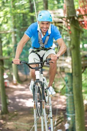 entertainment risk: Man riding bicycle on tightrope at high rope course