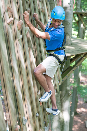 climbing  wall: Climber at climbing wall in high rope course