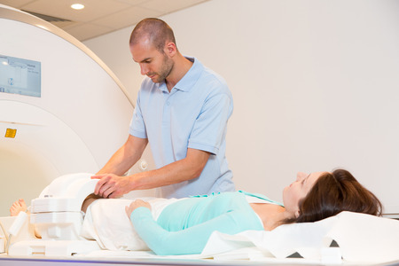 technical assistant: Medical technical assistant councelling patient and preparing scan of the knee with magnetic resonance tomography MRI in radiology Stock Photo