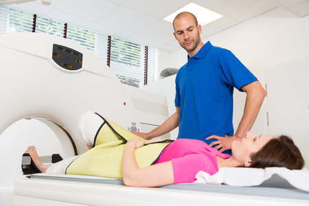 technical assistant: Medical technical assistant councelling patient and preparing scan of the spine with x-ray computed tomography CT in radiology