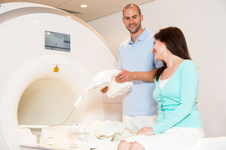 mri: Medical technical assistant councelling patient and preparing scan of the knee with magnetic resonance tomography MRI in radiology Stock Photo
