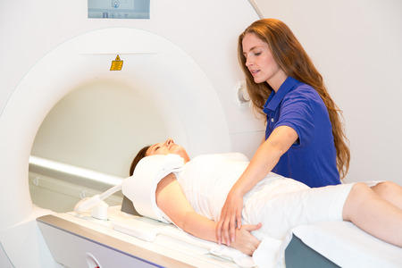 radiological: Medical technical assistant councelling patient and preparing radiological scan of the shoulder with magnetic resonance tomography MRI