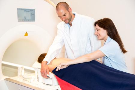 resonancia magnetica: Técnico auxiliar en consejo médico paciente y la preparación de exploración de la columna vertebral con magnética MRI tomografía de resonancia en radiología