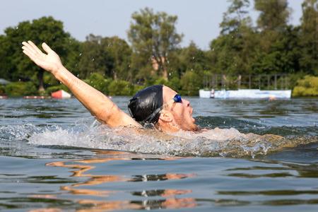 backstroke: Man swims backstroke in swimming pool or lake