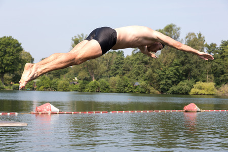 pool diving: Man jumping off diving board at a public swimming pool