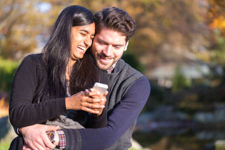 Couple in love looking at cellphone laughing photo