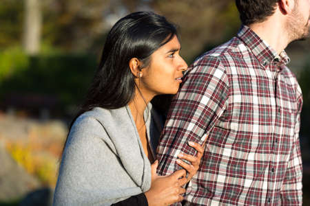holding arm: Woman holding arm of her rejecting partner Stock Photo