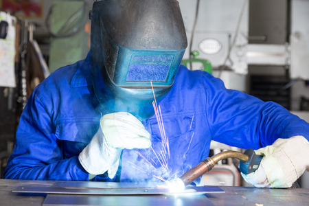 welding mask: professional welder welding metal pieces with light arc and sparks