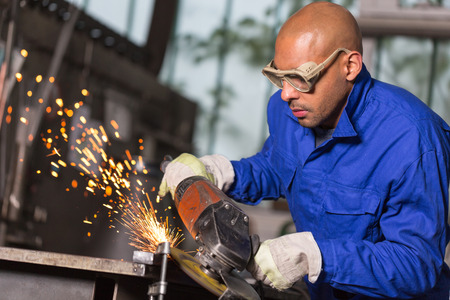 industrial building: worker grinding a piece of metal with angle gringer