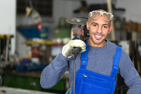 construction worker posing with angle grinder in a workshop