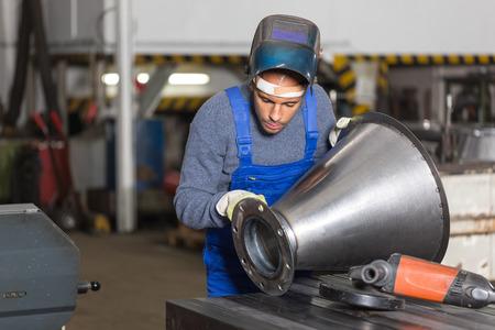 control de calidad: Soldador inspeccionar una pieza de metal para el control de calidad