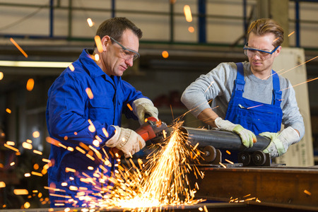 heavy industry: Two workers working with angle grinder in steel construction Stock Photo